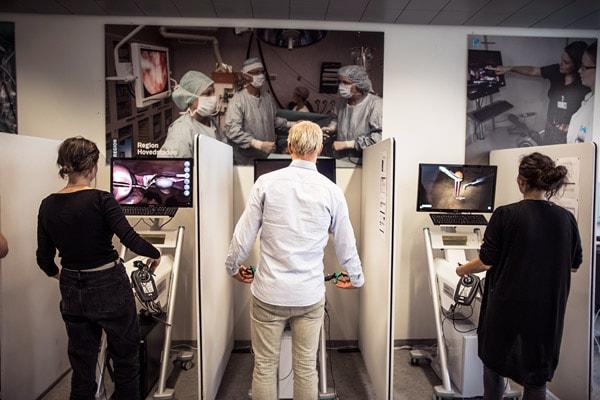Tre studerende træner forskellige procedurer på VR-simulationsmaskiner