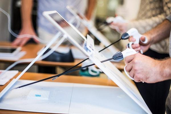 Studerende flytter perler med kirurgiske instrumenter